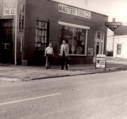 A historical photo of Charles Zeller and Francis Herr standing in front of the auto repair garage in Evansville Indiana.