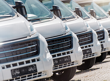 A fleet of vans in a line ready to be serviced.